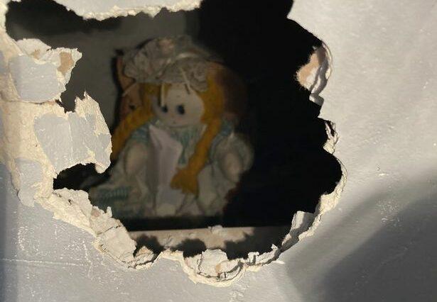 Doll behind wall